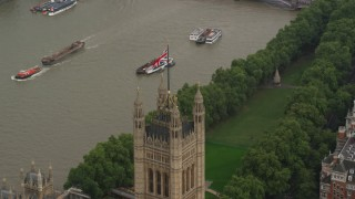 AX115_100 - 6K stock footage aerial video of British Flag atop Parliament beside River Thames, London England