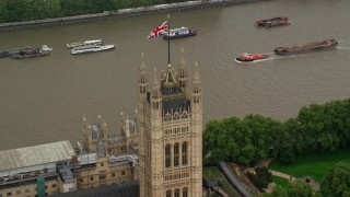 AX115_101 - 6K stock footage aerial video of orbiting British Flag atop Parliament along River Thames, London England