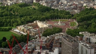 AX115_126 - 6K stock footage aerial video orbiting Buckingham Palace among trees, England