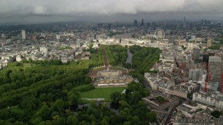 AX115_129 - 6K stock footage aerial video of orbiting Buckingham Palace with a cityscape view, London, England