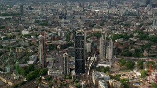 AX115_150 - 6K stock footage aerial video approach Strata skyscraper against sprawling cityscape, London, England