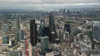 AX115_157 - 6K stock footage aerial video circle skyscrapers surrounded by city sprawl in Central London, England