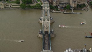 AX115_173 - 6K stock footage aerial video of boats on River Thames passing under Tower Bridge, London, England