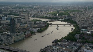 AX115_194 - 6K stock footage aerial video approach London Eye Ferris wheel and bridges over the Thames, London, England