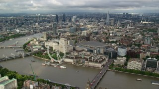 AX115_200 - 6K stock footage aerial video of London Eye and River Thames against the cityscape, London, England