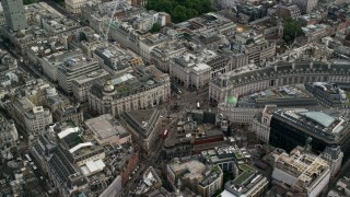 AX115_210 - 6K stock footage aerial video of flying by Piccadilly Circus with traffic and tourists, London, England