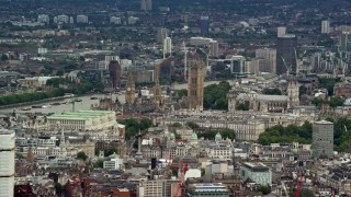 AX115_240 - 6K stock footage aerial video of a view of Big Ben and Parliament among city buildings, London, England