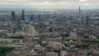 AX115_267 - 6K stock footage aerial video the London Eye and Parliament, with skyscrapers in the background, England