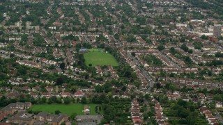 AX115_294 - 6K stock footage aerial video of orbiting a residential neighborhood and park, Wallington England