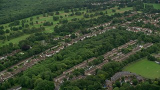 AX115_301 - 6K stock footage aerial video of passing residential neighborhoods and trees, Coulsdon, England