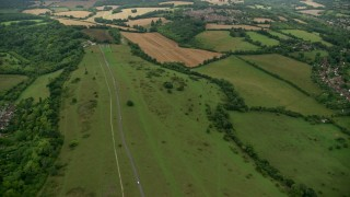 AX115_303 - 6K stock footage aerial video fly over country road and farmland, Coulsdon, England