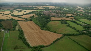 AX115_304 - 6K stock footage aerial video fly over farmland toward rural homes in a village, Coulsdon, England