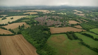 AX115_305 - 6K stock footage aerial video approach farmland and rural homes in a village, Coulsdon, England