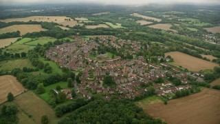 AX115_306 - 6K stock footage aerial video of orbiting rural homes and farmland, Coulsdon, England