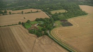 AX115_308 - 6K stock footage aerial video of orbiting a farm and fields, Redhill, England
