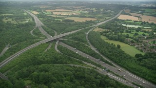 AX115_310 - 6K stock footage aerial video of orbiting trees around the M23 and M25 freeway interchange, Redhill, England