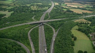 AX115_311 - 6K stock footage aerial video orbiting trees and the M23 / M25 freeway interchange, Redhill England