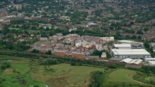 AX115_313 - 6K stock footage aerial video orbit apartment buildings and warehouses, reveal passing train in Redhill, England