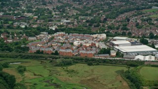 AX115_314 - 6K stock footage aerial video of apartment and warehouse buildings with a passing train, Redhill, England