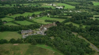 AX115_315 - 6K stock footage aerial video of Nutfield Priory Hotel with trees, Redhill, England
