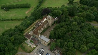 AX115_316 - 6K stock footage aerial video orbit Nutfield Priory Hotel with trees, Redhill, England