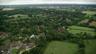 AX115_317 - 6K stock footage aerial video orbiting homes in a rural village, Redhill, England