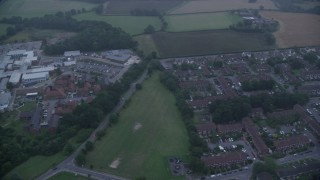 AX116_001 - 6K stock footage aerial video of flying by homes, East Surrey Hospital, Redhill, England, twilight