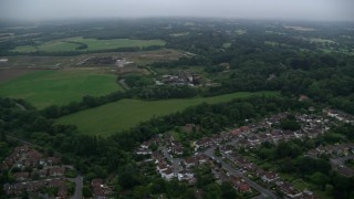 AX116_003 - 6K stock footage aerial video of flying by homes and Patteson Court Landfill Site, Redhill, England, twilight