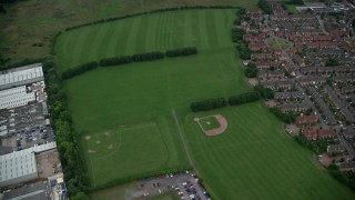 AX116_006 - 6K stock footage aerial video of flying away from sports fields, revealing warehouses in Croydon, England, twilight