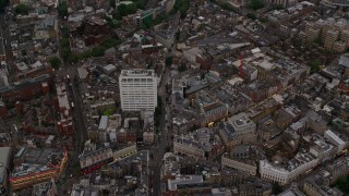 AX116_036 - 6K stock footage aerial video pan across Westminster city streets and office building, London, England, twilight