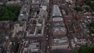 AX116_050 - 6K stock footage aerial video of flying over Oxford Street with double decker buses, London, England, twilight