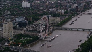 AX116_057 - 6K stock footage aerial video of flying by London Eye and Westminster Bridge over River Thames, London, England, twilight