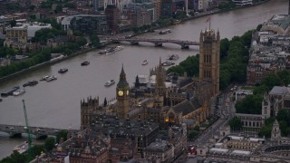 AX116_059 - 6K stock footage aerial video of flying by Big Ben and British Parliament on River Thames, London, England, twilight