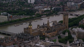 AX116_062 - 6K stock footage aerial video of passing by Big Ben and British Parliament overlooking River Thames, London, England, twilight