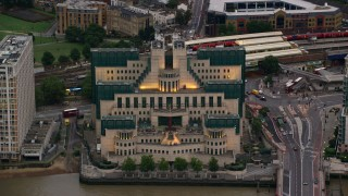 AX116_066 - 6K stock footage aerial video of the MI6 Building by the River Thames, London, England, twilight