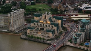 AX116_067 - 6K stock footage aerial video of flying away from MI6 Building by River Thames, London, England, twilight