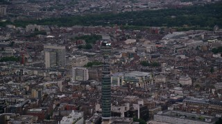 AX116_097 - 6K stock footage aerial video of flying by BT Tower, London, England, twilight