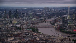 AX116_105 - 6K stock footage aerial video of bridges spanning River Thames near skyscrapers, London, England, night
