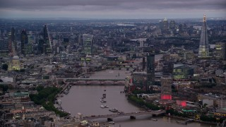 AX116_107 - 6K stock footage aerial video of bridges over River Thames, skyscrapers and cityscape, London, England, night
