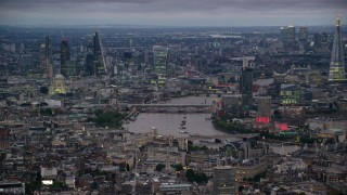 AX116_111 - 6K stock footage aerial video of bridges spanning River Thames between skyscrapers, London, England, night