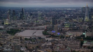 AX116_112 - 6K stock footage aerial video of towering skyscrapers and bridges spanning River Thames, London, England, night