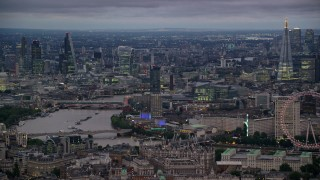 AX116_113 - 6K stock footage aerial video tall skyscrapers and River Thames bridges, reveal London Eye, London, England, night