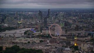 AX116_116 - 6K stock footage aerial video of vast cityscape seen from London Eye and Big Ben by River Thames, London, England, night