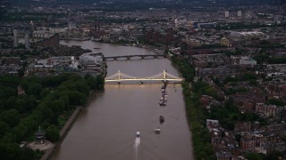 AX116_120 - 6K stock footage aerial video of approaching Albert Bridge spanning the River Thames, London, England, night