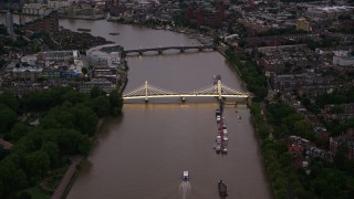 AX116_121 - 6K stock footage aerial video of an approach to Albert Bridge spanning River Thames, London, England, night