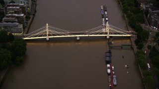 AX116_123 - 6K stock footage aerial video of Albert Bridge spanning the River Thames, London, England, night