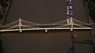 AX116_124 - 6K stock footage aerial video tilt to bird's eye view of Albert Bridge spanning River Thames, London, England, night