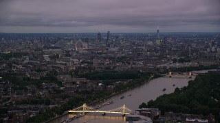 AX116_131 - 6K stock footage aerial video wide view of London from River Thames and Albert Bridge, England, night