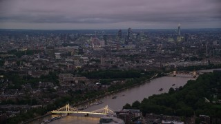 AX116_132 - 6K stock footage aerial video of River Thames, Albert Bridge and the London cityscape, England, night