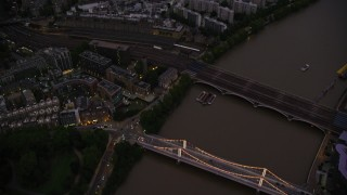 AX116_137 - 6K stock footage aerial video tilt from Chelsea Bridge and River Thames to reveal apartments and cityscape, London, England, night